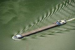 Pine ore barge - Danube Boilers. Danube river - landmark attraction in Romania. Pine ore barge passing Danube Boilers. Danube river - landmark attraction in royalty free stock image