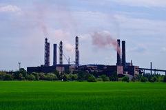 Ore-dressing factory. With industrial smoke on green meadow as foreground and blue sky as back Royalty Free Stock Image