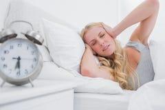 Orecchie bionde stanche della copertura della donna con le mani Immagine Stock