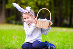 Orecchie d'uso del coniglietto della bambina adorabile che tengono un canestro con le uova di Pasqua il giorno di molla Fotografie Stock Libere da Diritti