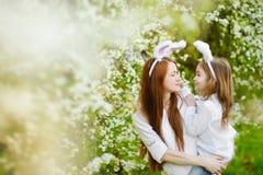 Orecchie d'uso del coniglietto della figlia e della madre su Pasqua Immagine Stock