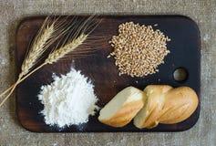 Orecchie del grano, grani, farina e pane affettato su un bordo della cucina su un fondo di licenziamento immagine stock