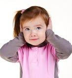 Orecchie della copertura della bambina con le mani Fotografia Stock
