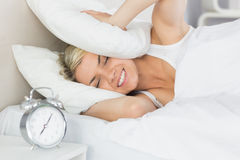Orecchie della copertura della donna con il cuscino e la sveglia in priorità alta Fotografia Stock