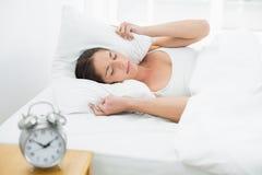 Orecchie della copertura della donna con il cuscino e la sveglia sulla tavola laterale Immagine Stock Libera da Diritti