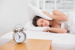 orecchie della copertura della donna con il cuscino a letto e la sveglia sulla tavola laterale Immagine Stock Libera da Diritti