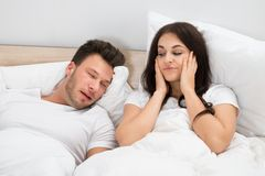 Orecchie della copertura della donna mentre uomo che russa sul letto Fotografia Stock