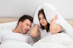 Orecchie della copertura della donna mentre uomo che russa sul letto a casa Fotografie Stock