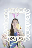 Orecchie di coniglio d'uso della bella giovane donna e tenere l'uovo di Pasqua giallo dello zecchino Immagini Stock Libere da Diritti