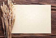 Orecchie di grano e del foglio di carta su vecchio legno. Fotografia Stock