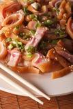 Orecchie fritte del maiale con i semi di sesamo su una macro del piatto verticale Fotografie Stock
