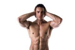 Orecchie senza camicia muscolari della copertura del giovane con le mani Fotografia Stock Libera da Diritti