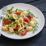 Orecchiette makaron z pomidorów, Parmezańskiej i rakietowej sałatką na, matrycuje światło Fotografia Stock
