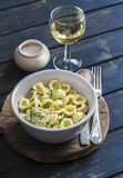 Orecchiette pasta with broccoli and pine nuts pesto and a glass of white wine on dark wooden background. Stock Photos