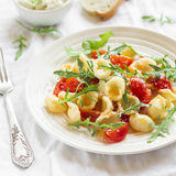 Orecchiette pasta with cherry tomatoes, arugula and Parmesan cheese on a white plate Stock Photo
