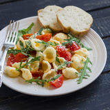 Orecchiette pasta with cherry tomatoes, arugula and Parmesan on a plate light Royalty Free Stock Photo