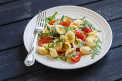 Orecchiette pasta with tomatoes, Parmesan and rocket salad Royalty Free Stock Photo