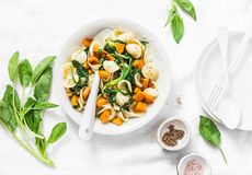 Orecchiette-Teigwaren mit Spinat und Kürbis - vegetarisches Mittagessen auf weißem Hintergrund lizenzfreie stockfotografie