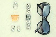 Orecchini, anello, bottiglia di profumo, orologi fotografia stock