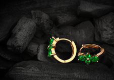 Orecchini dei gioielli con lo smeraldo della gemma sul fondo scuro del carbone, molle Fotografie Stock