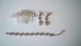 Orecchini dei gioielli della donna, braccialetto e clip di capelli stock footage