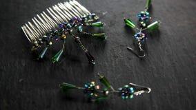 Orecchini dei gioiellieri e un pettine di straripamento fatto a mano e di filatura video d archivio