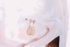 Orecchini dorati degli accessori femminili di nozze sopra il fondo bianco di velo Fotografie Stock Libere da Diritti