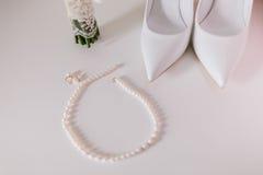 Orecchini e collana della perla di nozze vicini su con le scarpe di nozze Immagini Stock