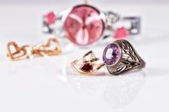 Orecchini ed anelli dell'oro con i rubini e l'orologio rossi Immagine Stock