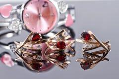 Orecchini ed anelli dell'oro con i rubini e l'orologio rossi Immagini Stock Libere da Diritti
