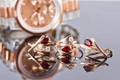 Orecchini ed anelli dell'oro con i rubini e l'orologio rossi Immagine Stock Libera da Diritti