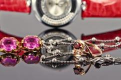Orecchini ed anelli dell'oro con i rubini e l'orologio rossi Fotografia Stock Libera da Diritti