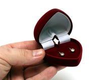 Orecchini gifting della mano dell'uomo in casella rossa Fotografia Stock