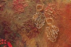 Orecchini openwork dell'oro su un fondo pittoresco di terracotta fotografie stock libere da diritti