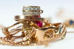 Orecchino dell'oro sugli anelli e sulla catena di oro Fotografie Stock