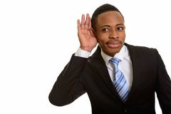 Orecchio d'ascolto e foggiante a coppa del giovane uomo d'affari africano bello fotografia stock