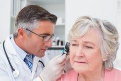 Orecchio d'esame dei pazienti di medico con l'otoscopio immagine stock libera da diritti