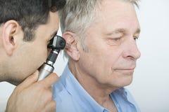 Orecchio del dottore Checking Patient facendo uso dell'otoscopio immagini stock