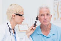 Orecchio maschio d'esame dei pazienti di medico con l'otoscopio immagine stock