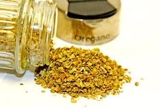 Oregano. Dried flakes of oregano leaves poured of a small glass jar Stock Photo