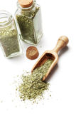 Oregano. Spice, wooden spoon and two glass bottles Stock Photos