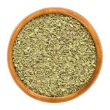 Oregano dried in wooden bowl over white. Oregano dried in wooden bowl. Origanum vulgare, sometimes wild marjoram. Herb with aromatic olive green leaves and a Stock Images