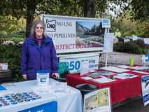 Oregon climate activist poses beside no-LNG information table at Royalty Free Stock Photo