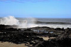 Oregon Coast Afternoon. Coastal waves break and splash on dark rocky outcrops against clear blue Oregon sky Stock Image