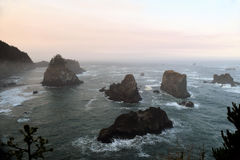 Oregon Coast Morning. Hazy pinkish morning along the Oregon Coast with huge rock formations among ocean waves Stock Photo