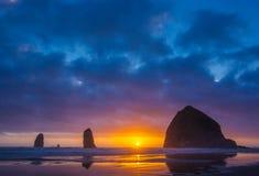Oregon Coast. Sun Setting Behind Haystack Rock And Needles In Cannon Beach, Oregon Stock Photo