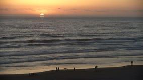 Oregon Coast Sunset, Cannon Beach 4K. UHD. People enjoying the sunset in Cannon Beach, Oregon as the surf washes up onto the beach. United States. 4K, UHD stock video footage