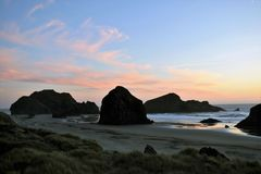 Oregon Coast Sunset. Pink cloud sunset in blue sky over rock formations and ocean on Oregon coast Royalty Free Stock Photography