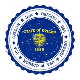 Oregon flag badge. Grunge rubber stamp with Oregon flag. Vintage travel stamp with circular text, stars and USA state flag inside it. Vector illustration Royalty Free Stock Images