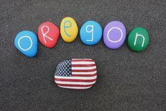 Oregon, United States of America, souvenir with colored stones and USA flag over black volcanic sand. Oregon is a state in the Pacific Northwest region on the Stock Photo